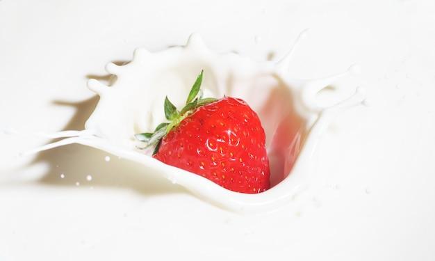 Fresas caer en la leche con salpicaduras Foto Premium
