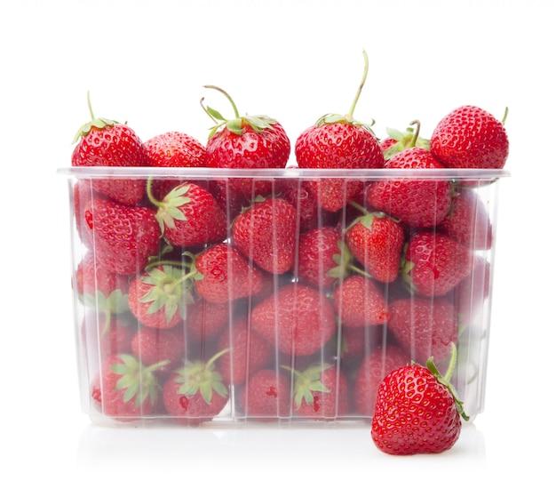 Fresas frescas en caja de plástico de frutas en blanco Foto Premium