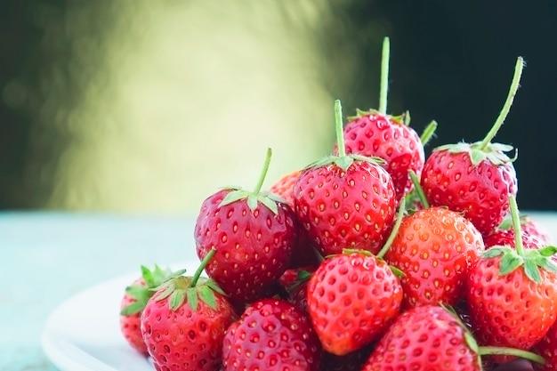 Fresas frescas sobre fondo claro degradado dorado Foto gratis