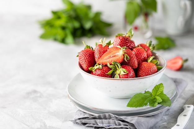 Fresas frescas en un tazón y ramitas de menta en una mesa de hormigón blanco. ingrediente para batidos. Foto Premium