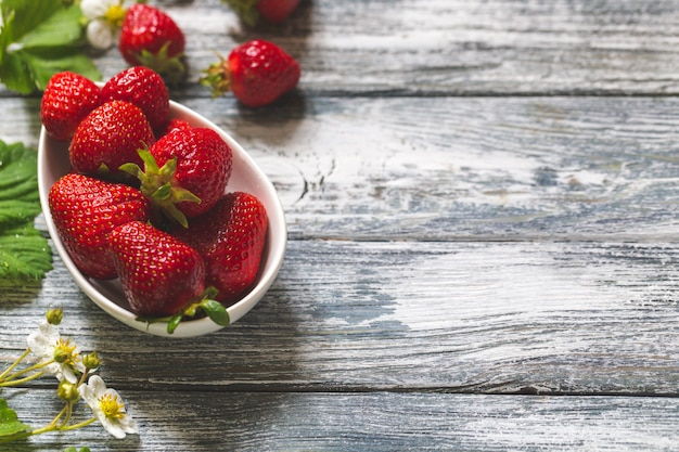 Fresas jugosas frescas con hojas en un tazón Foto Premium