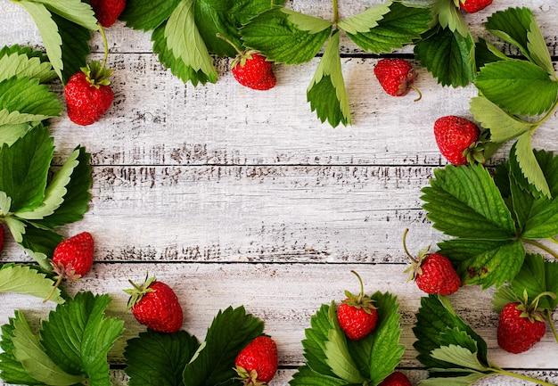 Fresas maduras y marco de hojas sobre fondo de madera. vista superior Foto Premium