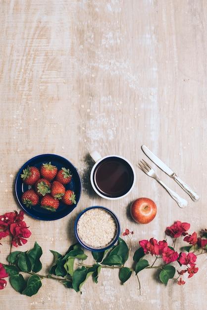 Fresas; taza de café; avena; manzana entera y cubiertos con flores de buganvilla sobre fondo de madera Foto gratis
