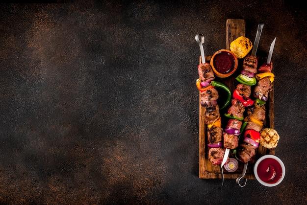Fresco, cocinado en casa a la parrilla carne de fuego shish kebab de carne con verduras y especias, con salsa de barbacoa y salsa de tomate, sobre un fondo oscuro sobre una tabla de cortar de madera sobre espacio de copia Foto Premium