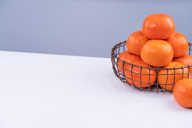 Fresco hermoso kaki caqui dulce en rodajas aislado en la mesa de la cocina blanca con fondo azul gris, concepto de diseño de año nuevo lunar chino, de cerca. Foto Premium