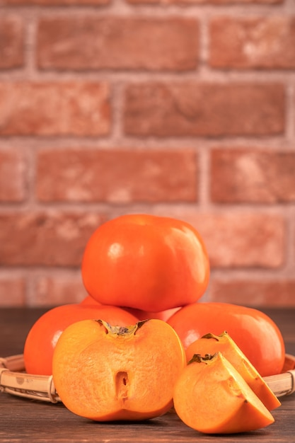 Fresco y hermoso kaki dulce caqui en rodajas en la mesa de madera oscura con fondo de pared de ladrillo rojo, concepto de diseño de fruta de año nuevo lunar chino, de cerca. Foto Premium