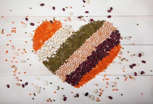 Frijoles, lentejas y frijoles dispuestos en forma de corazón sobre un fondo blanco de madera Foto Premium