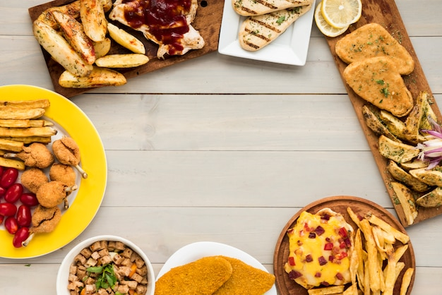 Frontera hecha de platos de pollo de comida rápida en mesa de madera Foto gratis