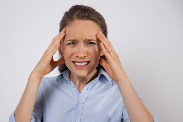 Fruncir el ceño a empresaria sufriendo de dolor de cabeza Foto gratis
