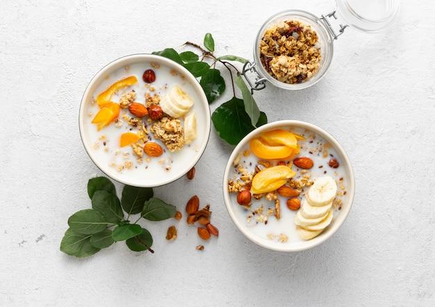 Fruta de granola con leche, mantequilla de maní en un tazón, cereales para el desayuno saludable vista superior Foto Premium