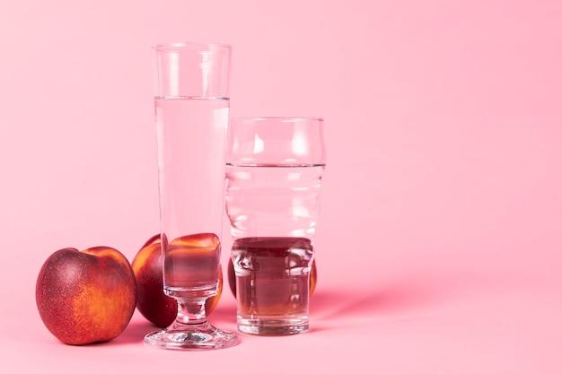 Fruta de nectarina y vasos de agua. Foto gratis