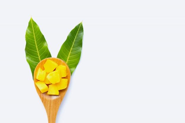Fruta tropical, rodajas de cubo de mango con cuchara de madera y hojas sobre fondo blanco. Foto Premium