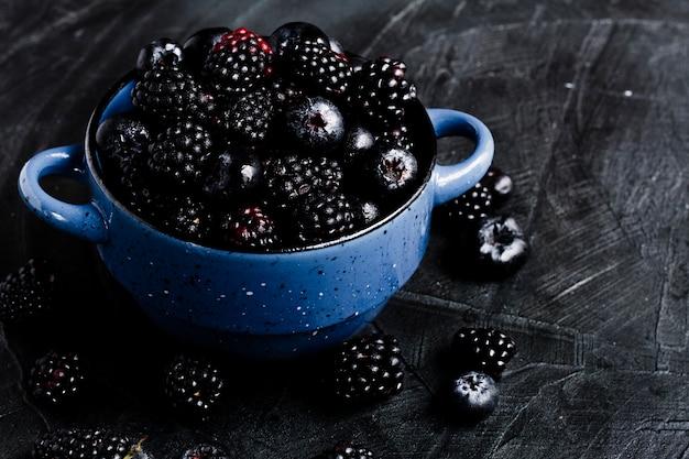 Frutas del bosque negro de alto ángulo en maceta Foto gratis