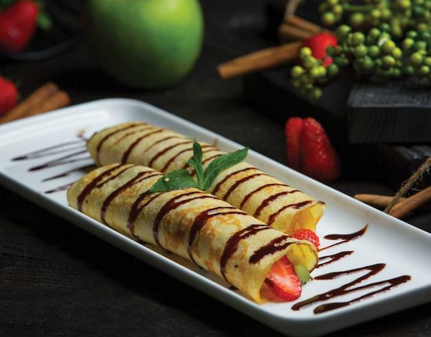 Frutas envueltas en crepes y salsa de chocolate. Foto gratis