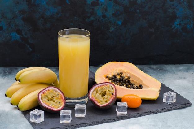Frutas exóticas, cubitos de hielo y un vaso de jugo. Foto Premium
