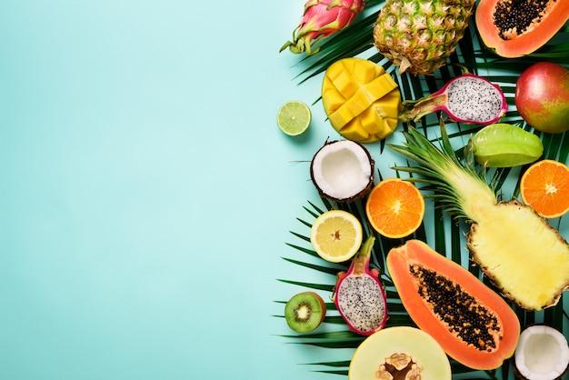 Frutas exóticas y hojas de palma tropical - papaya, mango, piña, plátano, carambola, fruta del dragón, kiwi, limón, naranja, melón, coco, lima. Foto Premium