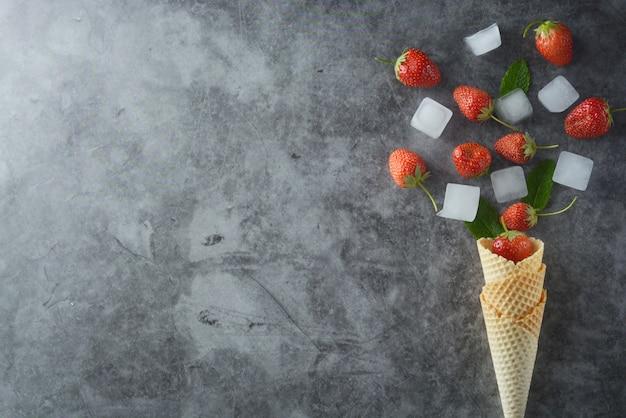 Frutas de la fresa en cono de la galleta sobre la opinión superior del fondo oscuro Foto Premium