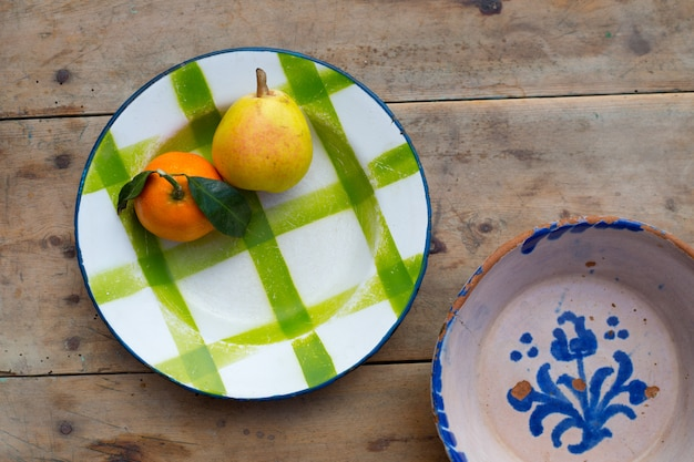 Frutas mandarina y pera en plato de porcelana vintage Foto Premium