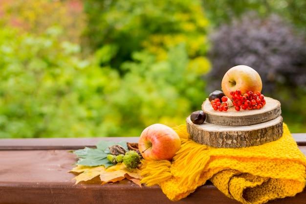 Frutas y nueces, bufanda amarilla sobre la mesa de madera Foto Premium