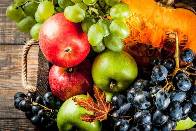 Frutas de otoño estacionales y calabaza en mesa de madera Foto Premium