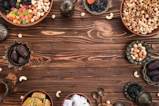 Frutas secas; fechas; lukum y baklava preparados para ramadan en mesa de madera Foto gratis