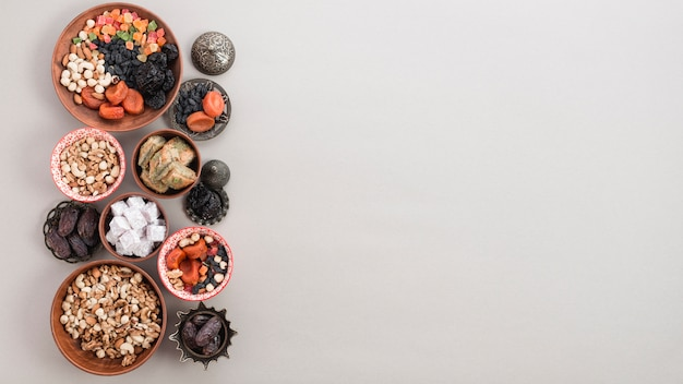 Frutas secas; nueces; fechas; lukum y baklava sobre fondo blanco con espacio para escribir el texto Foto gratis