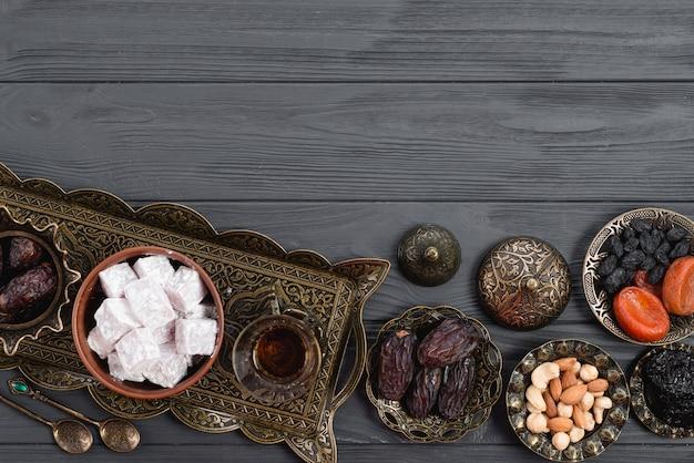 Frutas secas; nueces; fechas; lukum y té en ramadán sobre el escritorio de madera Foto gratis