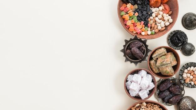 Frutas secas tradicionales turcas; nueces; lukum y baklava sobre fondo blanco Foto gratis