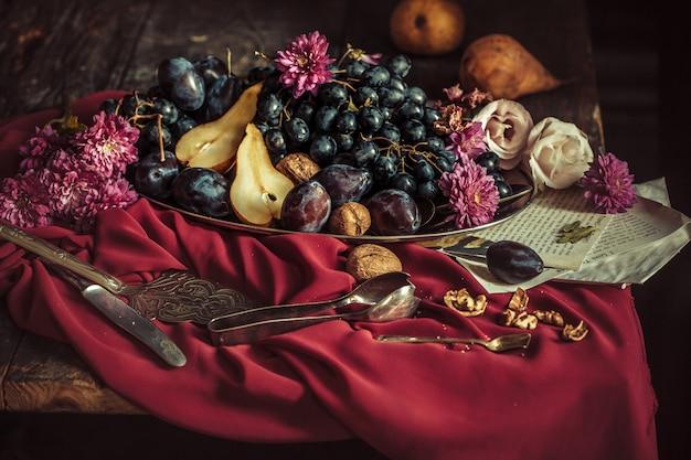 El frutero con uvas y ciruelas contra un mantel marrón Foto gratis