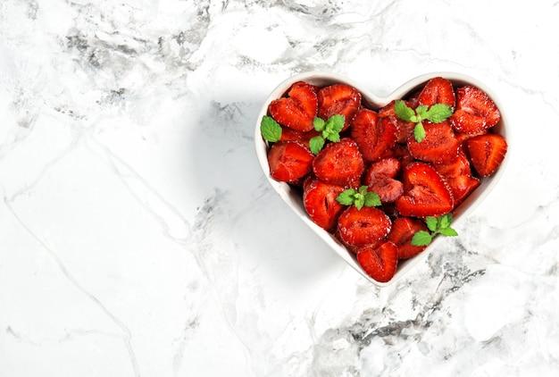 Frutos de fresa en un tazón en forma de corazón Foto Premium