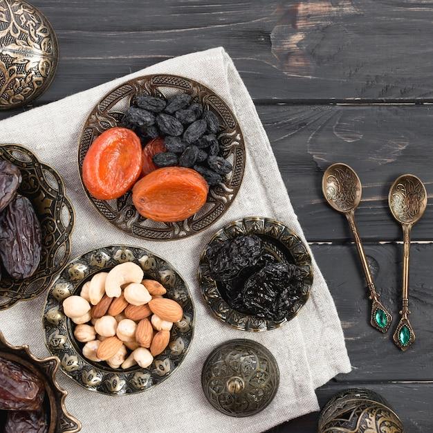 Frutos secos y nueces; fechas para ramadan con cucharas sobre el escritorio de madera Foto gratis