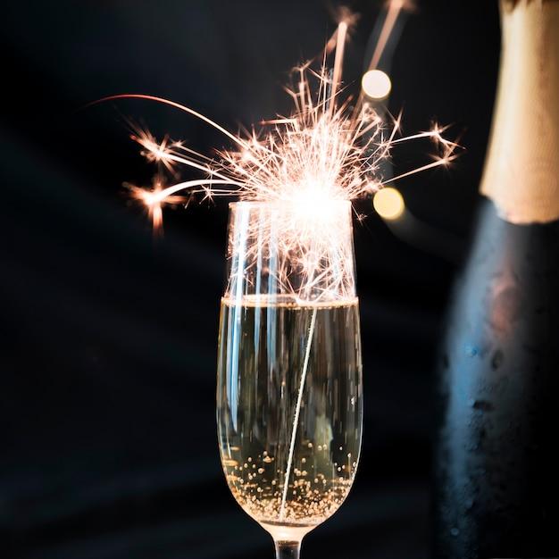 Fuego de bengala ardiendo en copa de champán Foto gratis