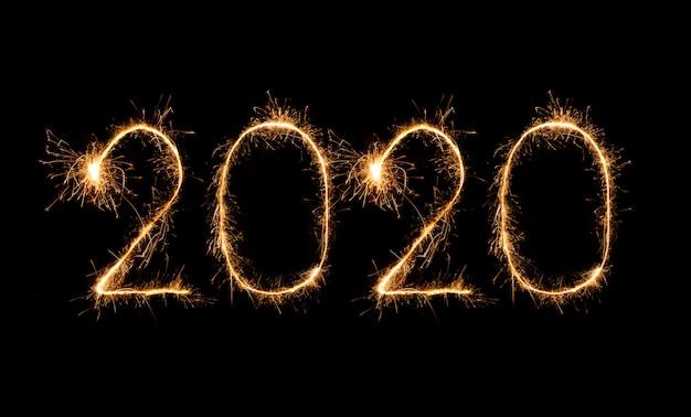Fuegos artificiales de feliz año nuevo 2020 escritos con bengalas en la noche Foto Premium