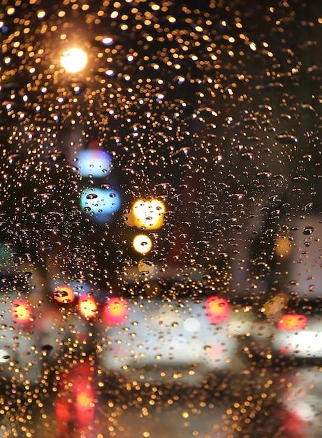 Fuera de foco del atasco de tráfico en la noche lluviosa vista desde el parabrisas de un automóvil con gotas de lluvia Foto Premium