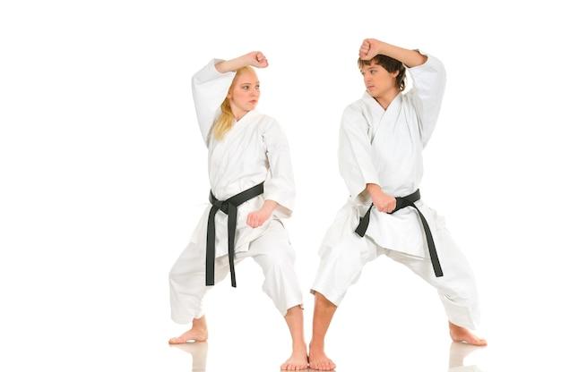 Fuerte joven rubia y el descarado chico de karate se dedican a entrenar en un kimono sobre un fondo blanco. Foto Premium