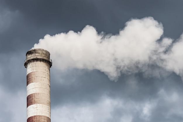 Fumar chimenea industrial en nubes oscuras. concepto para la protección del medio ambiente. Foto Premium