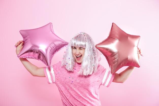 Funny girl con cabello plateado da una sonrisa y emoción en rosa. joven mujer o niña adolescente con globos y confeti Foto gratis