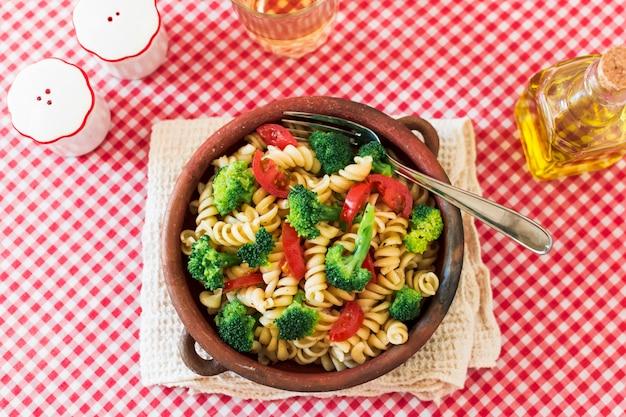 Fusilli de pasta vegetariana con tomate y brócoli sobre mantel Foto gratis