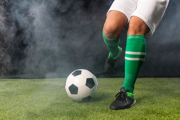 Futbolista en ropa deportiva pateando pelota Foto gratis