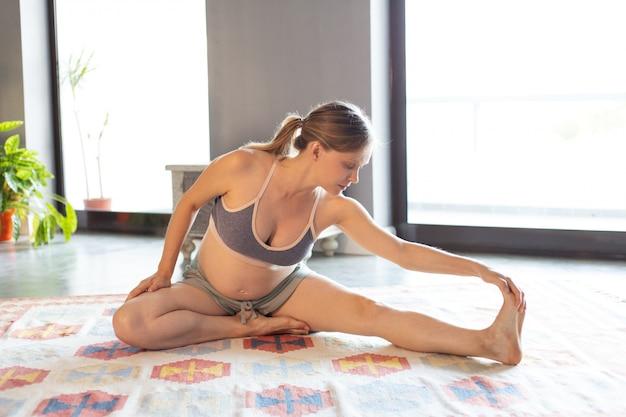 Futura madre haciendo yoga en casa Foto gratis