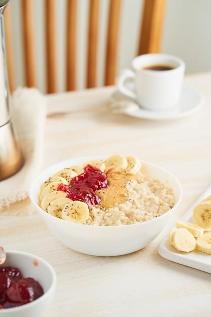 Gachas de avena, dieta saludable vegetariana desayuno con mermelada de fresa, mantequilla de maní, plátano, Foto Premium