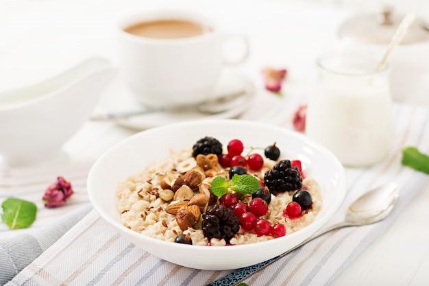 Gachas de avena sabrosas y saludables con bayas, semillas de lino y nueces. desayuno saludable. comida de fitness. nutrición apropiada. Foto gratis