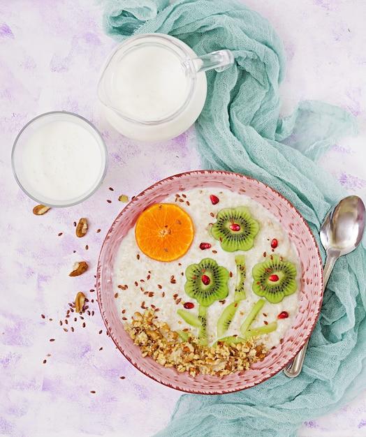 Gachas de avena sabrosas y saludables con kiwi, granada y nueces. desayuno saludable. comida de fitness. nutrición apropiada. vista superior Foto Premium
