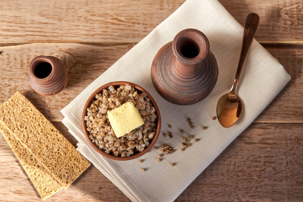 Gachas de trigo sarraceno con mantequilla en un tazón de madera blanca Foto Premium