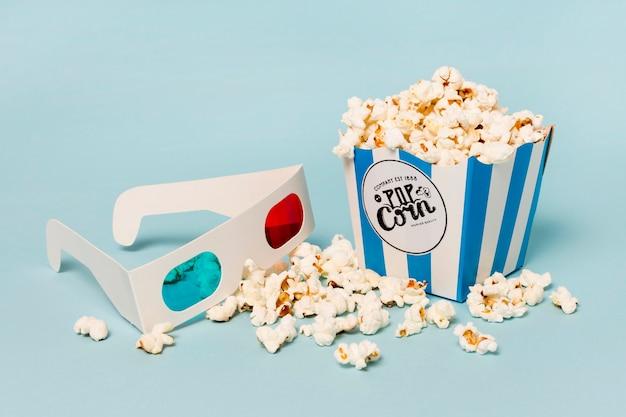 Gafas 3d con caja de palomitas de maíz sobre fondo azul Foto gratis