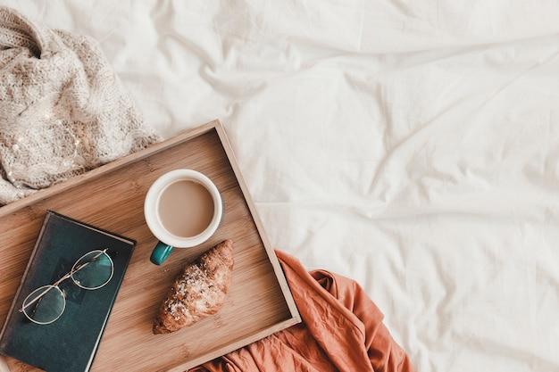 Gafas y libro cerca de la comida del desayuno en la cama Foto gratis