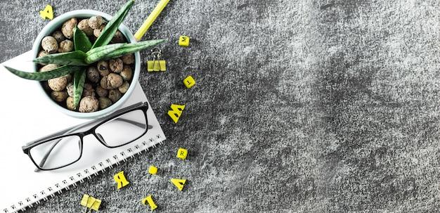 Gafas libros de profesor, letras de madera y una olla suculentas sobre la mesa, en el fondo de una pizarra con tiza. el concepto del día del profesor. copia espacio Foto Premium