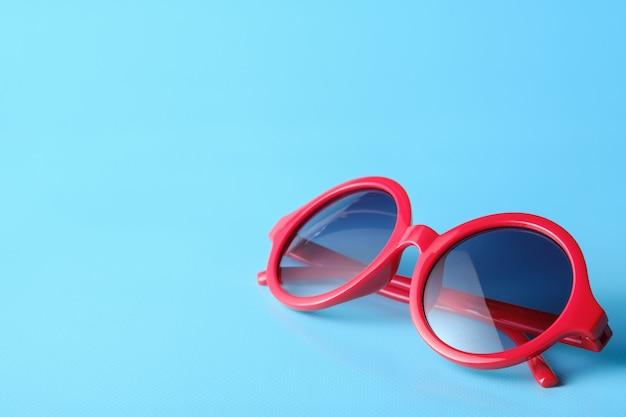 Gafas rojas sobre fondo azul con espacio de copia Foto Premium