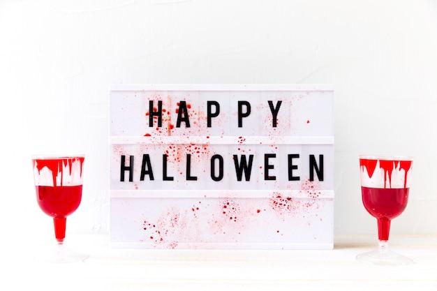 Gafas con sangre falsa cerca de la escritura feliz de halloween Foto gratis