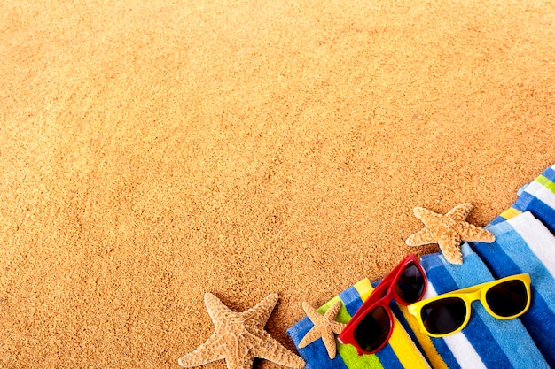 Gafas de sol de color sobre una toalla de playa Foto gratis